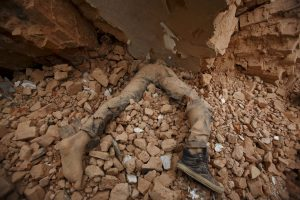 Body of a victim lies trapped in the debris after an earthquake hit, in Kathmandu